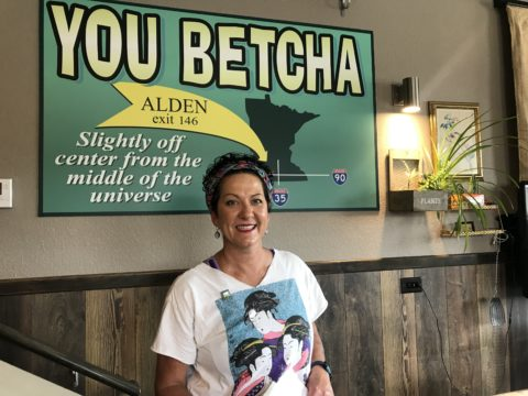 Julie Marschalk in front of sign pointing to location of You Betcha Cafe in Alden, MN